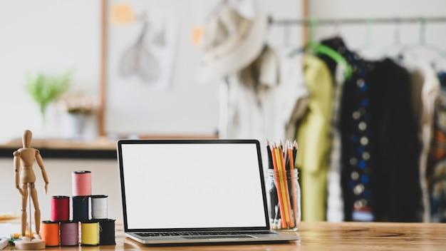 Дизайнер моды рабочей области с портативным компьютером, резьбой, карандашем и фиктивной древесиной на столе.
