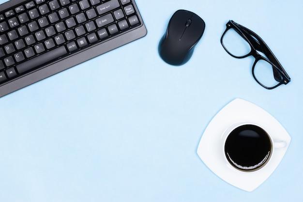 Рабочее пространство плоская планировка клавиатура с компьютерной мышью в очках чашка кофе на офисном столе копирование пространства