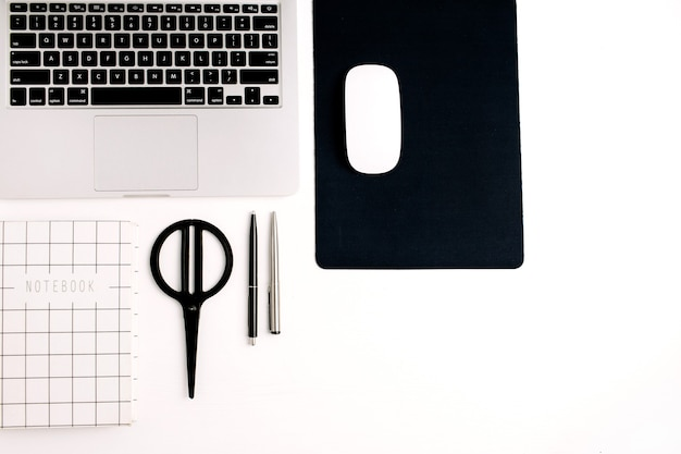 Workspace flat lay. laptop, mouse, notebook, pen and scissors on white background. top view home office concept.