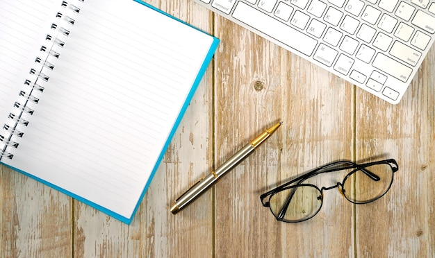 키보드 안경 및 공급품이 있는 흰색 나무 테이블 작업을 위한 작업 공간 평면 배치 구성