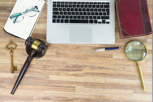 Workspace hero header with law gawel, legal book and laptop keyboard, top view, copy space on wooden table desktop background