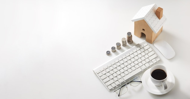 Workspace for house savings plans for housing, coin stack for living, home and real estate concepts.
