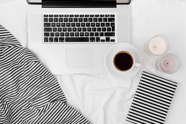 Рабочее место в постели с ноутбуком и кофе. утренняя концепция. плоская планировка