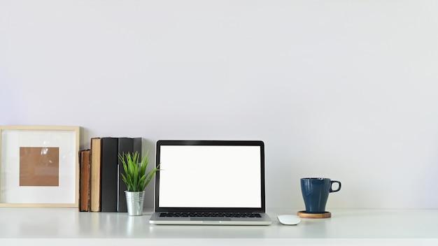 Портативный компьютер рабочей области, книга, рамка для фотографий и кружка кофе с горшком завода на копии делают интервалы между белой таблицей.