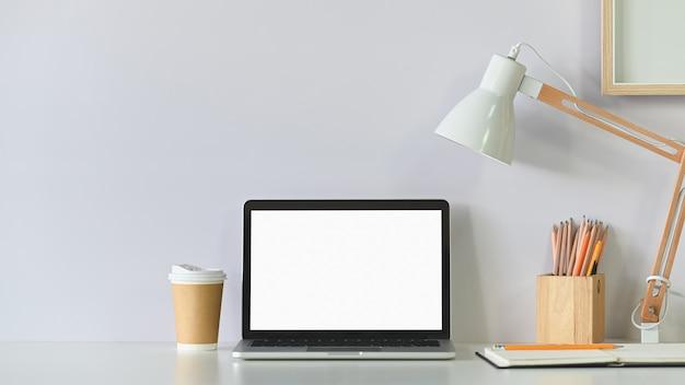 ワークスペースのラップトップコンピューター、コーヒー、鉛筆、白いテーブルの上のランプ付きフォトフレーム。