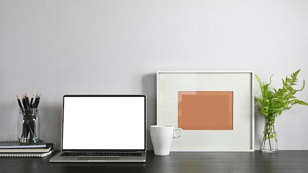 흰색 빈 화면, 연필 홀더, 액자, 화분, 노트북 및 커피 컵 스택 흰색 벽과 현대 나무 테이블에 함께 작업 공간 노트북