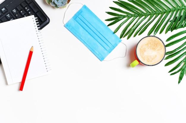 キーボード、メモ帳、カプチーノコーヒーカップと花の葉のあるワークスペースレイアウト。フラットレイ