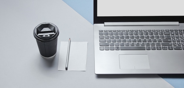 Workspace minimal concept. notebook, sheet of paper with a pencil, cardboard container of coffee on blue gray background
