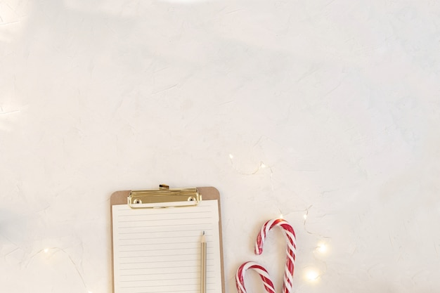 Workspace mockup, clipboard with blank paper, candy canes.