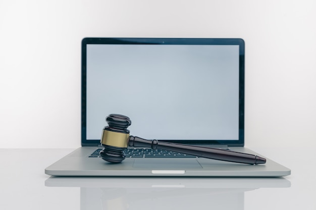 Рабочее пространство юриста с пустым белым экраном ноутбука и деревянным молотком закона, юридическая книга