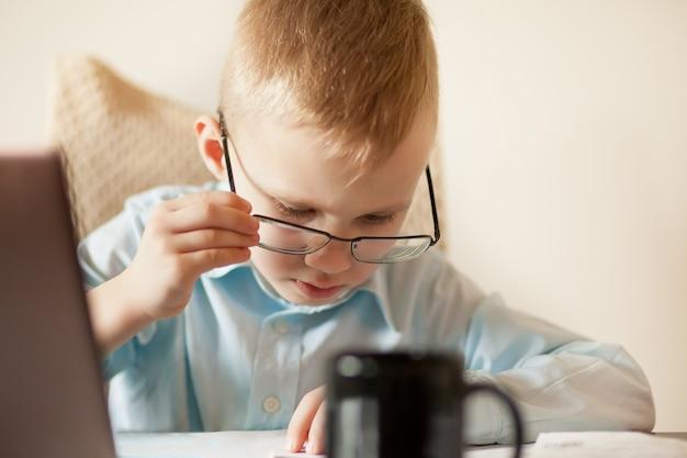 ノートパソコンと一杯のコーヒーとワークスペースのオフィスデスク。テーブルに座っていると重要なドキュメントを探しているかわいいビジネス少年。子供のオンライン学習。