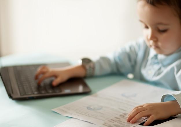 ノートパソコンとワークスペースのオフィスデスク。テーブルに座って、重要なドキュメントを探しているかわいいビジネスの少女。子供のオンライン学習。