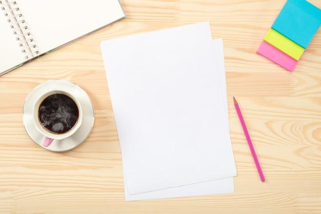 白紙の紙と木製のテーブルの上のワークスペース。木製のオフィステーブルのデスクトップミックス。フラットレイ