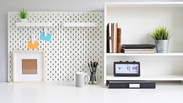 Workspace pegboard and shelves with office supplies