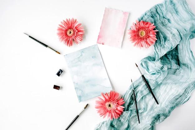 ワークスペース。ピンクのガーベラのつぼみと白地に絵筆と青い布の水彩紙