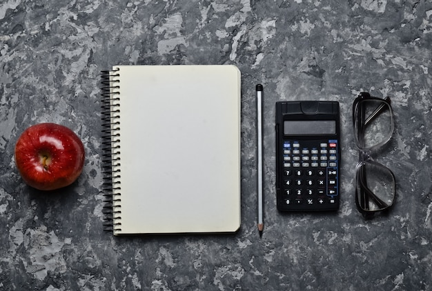 Workspace of a student engineer on a concrete surface. loft style. notepad, apple, calculator, pencil, glasses, ruler. minimalism and trend of gray color. top view. flat lay.