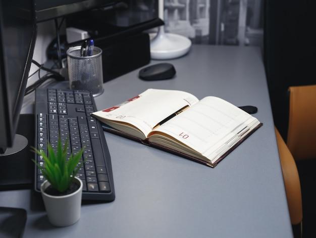 ペン付きワークスペーステーブル、スケジュールカレンダー。ラップトップコンピューターのある職場。ホームオフィスの構成。フリーランスの仕事、リモートワーク、インターネットサーフィン、ネットワークサービス、マーケティング、金融、ビジネス