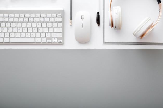 작업 공간 상위 뷰입니다. 키보드가 있는 사무실 테이블 책상, 회색 매트가 있는 흰색 테이블에 헤드폰 마우스 사무용품. 복사 공간이 있는 평평한 현대적인 작업 공간.