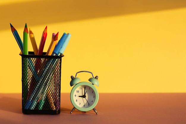 Рабочее пространство с будильником и канцелярскими товарами на желтом фоне. снова в школу. школьные инструменты, копия пространства