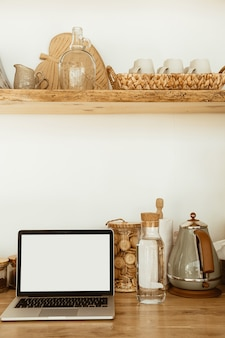 キッチンに空白のコピースペース画面のラップトップを備えたワークスペース。モダンでスタイリッシュなインテリアデザイン
