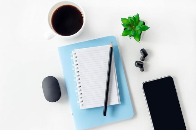 書き込みと鉛筆のための空白の開いているノートブックを持つワークスペース