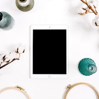 空白の画面タブレットと白い背景に綿を持つワークスペース。フラットレイ、トップビュー