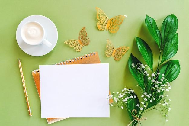 Рабочая область с чистого листа блокнота, карандаш, зеленый лист, декоративные золотые бабочки и чашка кофе на зеленом фоне