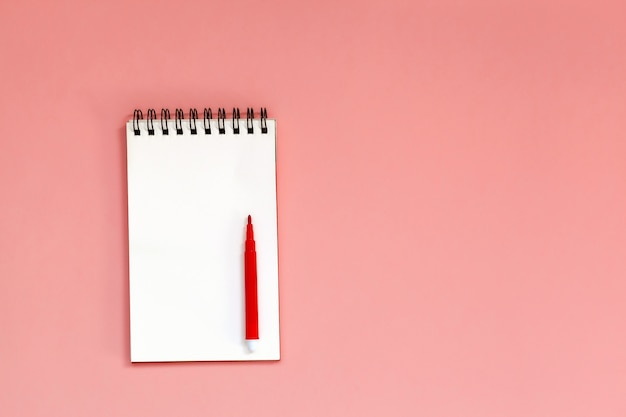 Workspace with blank spiral notebook with red pen on coral