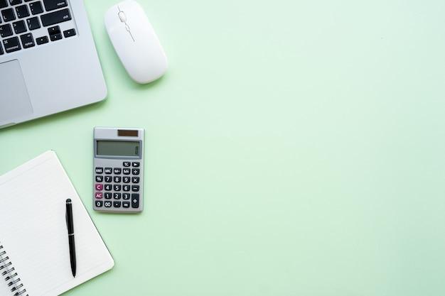Рабочее пространство с калькулятором, ручкой, ноутбуком, примечанием на пастельно-зеленом фоне.