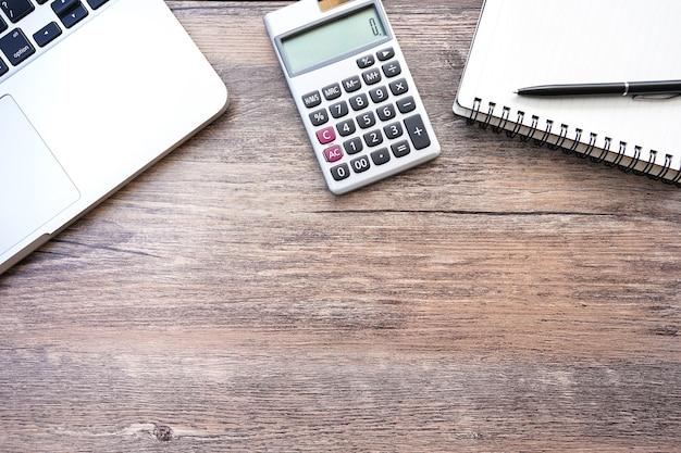 Рабочее пространство с калькулятором, ручкой, ноутбуком на старом деревянном фоне.