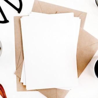 깨끗한 종이 빈, 커피, 공예 봉투, 가위, 흰색 표면에 사무용품이있는 작업 공간