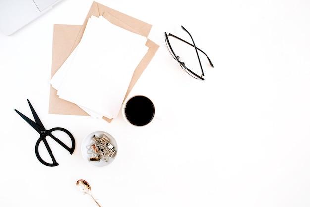 Рабочее пространство с кофе, ремесленным конвертом, ножницами, бланком для бумаги и ноутбуком на белой поверхности