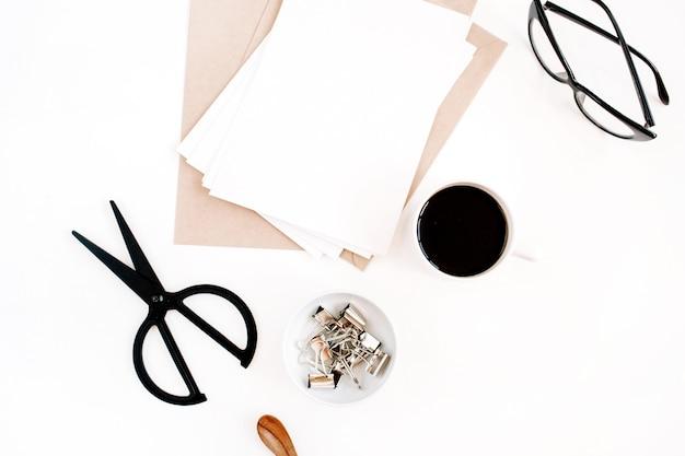 커피, 공예 봉투, 가위, 흰색 표면에 빈 종이가있는 작업 공간