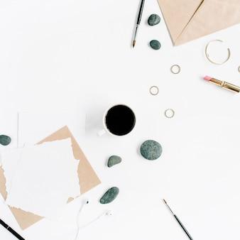 커피, 공예 봉투, 돌, 여성 액세서리 및 흰색 표면에 빈 종이가있는 작업 공간