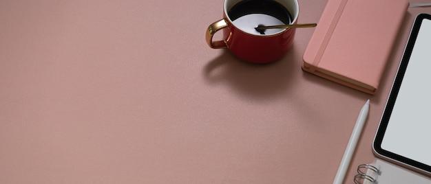 Рабочее пространство с чашкой кофе, макетом планшета, канцелярскими принадлежностями и копией пространства на розовом столе