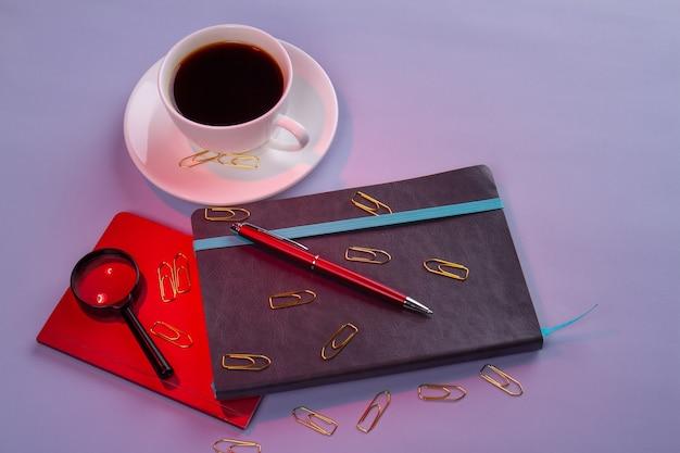 一杯のコーヒーとペンで本のあるワークスペース。紫色の背景に分離。