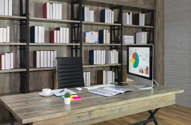 木製の机の上にデスクトップコンピューターと背景に本棚が付いた黒い椅子のあるワークスペース