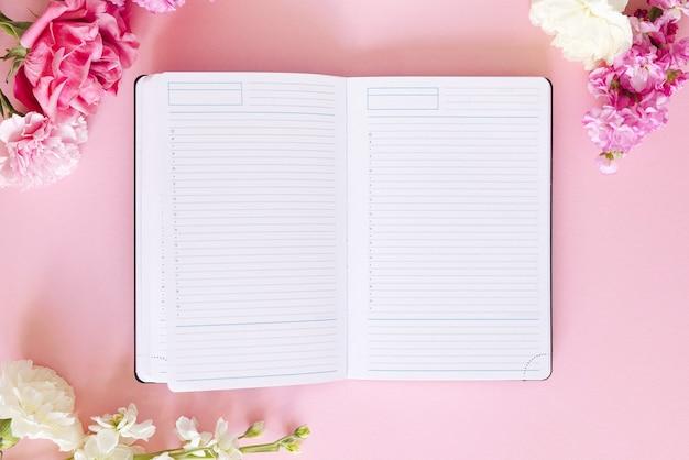 パステルカラーの背景に日記とピンクの白い花とワークスペース。上面図、フラットレイ