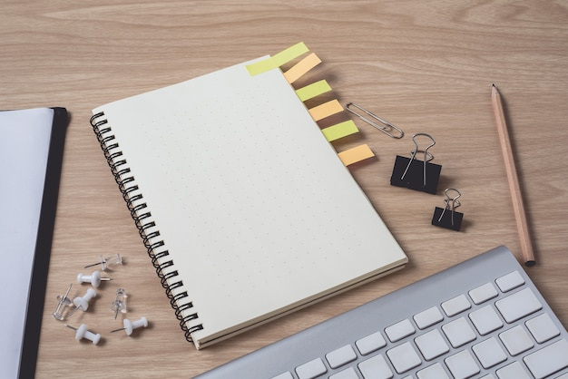 Workspace with diary or notebook and clipboard, keyboard, pencil, sticky notes