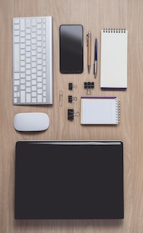 Workspace with diary or notebook and clipboard, laptop, mouse computer, keyboard, smart phone, pencil, pen