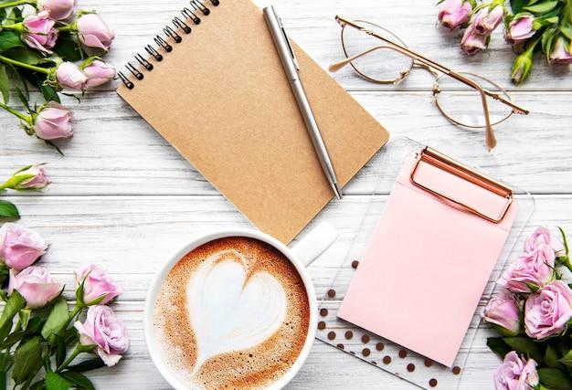 日記、ノート、クリップボード、白い背景の上のバラのワークスペース。ホームオフィスデスク。トップビューのフェミニンな背景。フラットレイ、上面図。