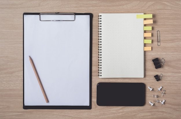 Workspace with diary or notebook and smart phone, clipboard, pencil, sticky notes on wooden