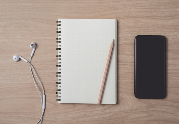 Workspace with diary or notebook and smart phone, earphone, pencil, pen on wooden