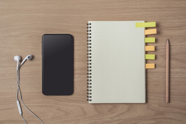 Workspace with diary or notebook and smart phone, earphone, pencil, sticky notes on wooden