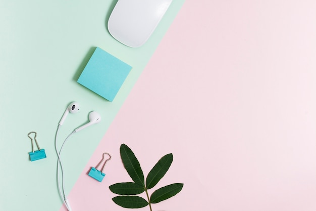 Workspace with earphones and mouse on pink and green background