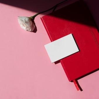 Рабочее пространство с пустой белой визиткой, макет пиона и красный блокнот