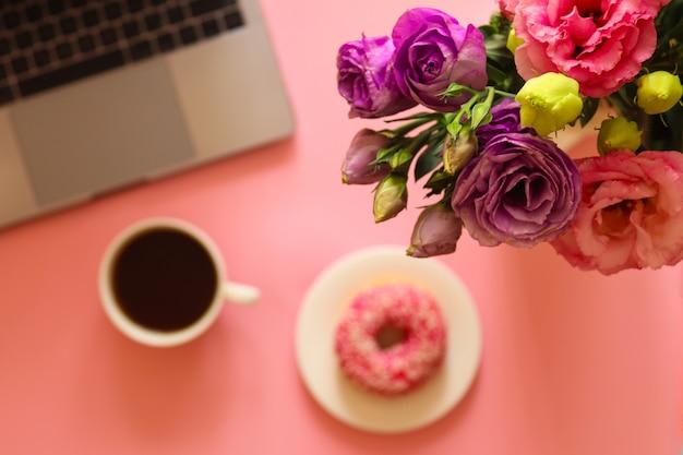 花、ラップトップ、ドーナツ、コーヒーのあるワークスペース
