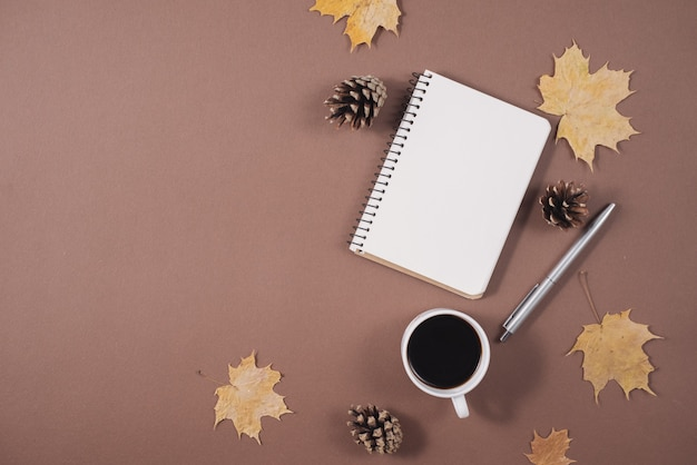 Workspace with golden maple leaves, coffee cup, bumps, notebook and pen on brown background.
