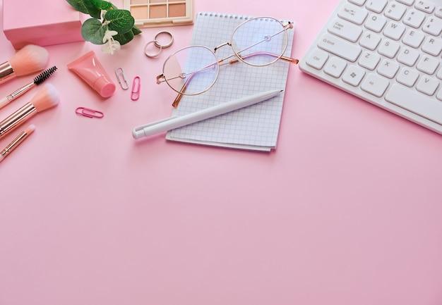 ピンクの表面にキーボード、メモ帳、メガネ、ペン、美容アクセサリーを備えたワークスペース