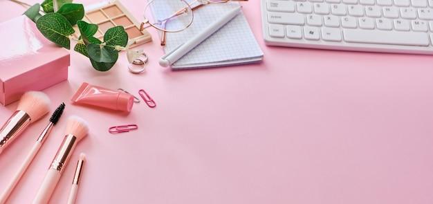 ピンクの表面コンセプトにキーボード、メモ帳、メガネ、ペン、美容アクセサリーを備えたワークスペース